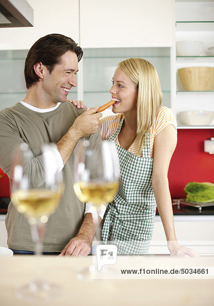 Mann füttert Frau mit einer Möhre