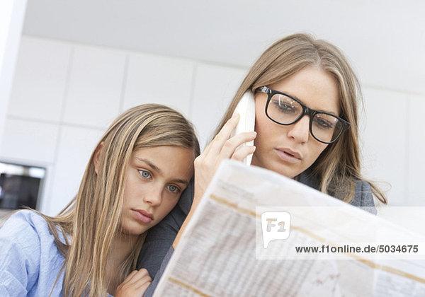 Mutter liest Zeitung und telefoniert mit Tochter an ihrer Seite