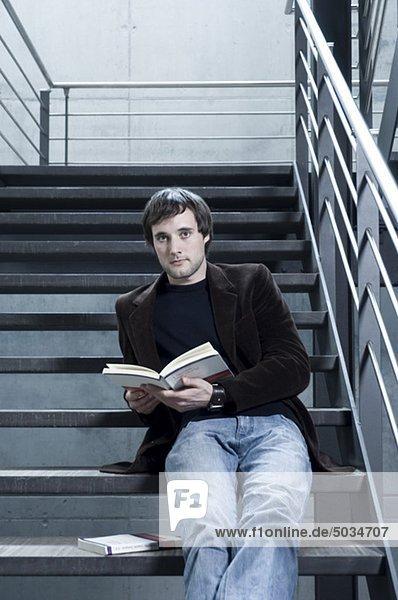 Junger Mann liest ein Buch im Treppenhaus