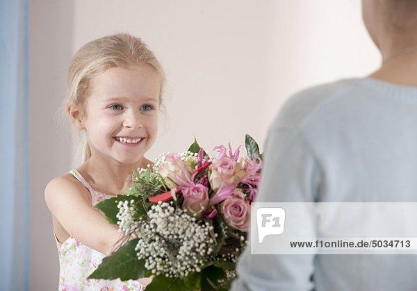Lächelndes Mädchen überreicht Mutter einen Blumenstrauß