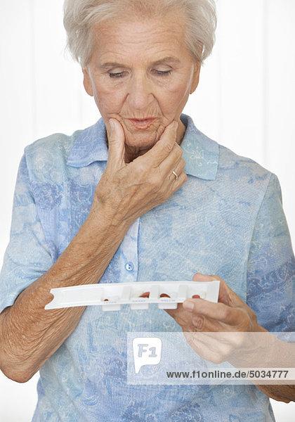 Seniorin schaut ratlos auf ihre Pillendose