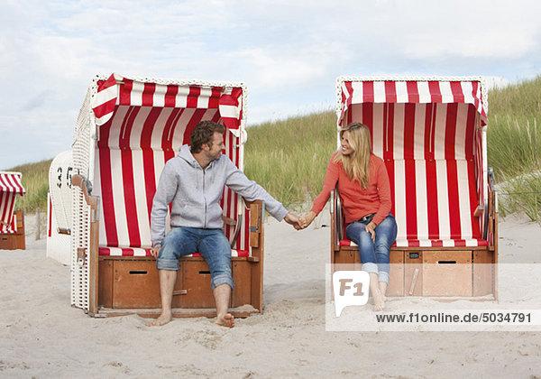 Paar sitzt Hand in Hand in Strandkörben