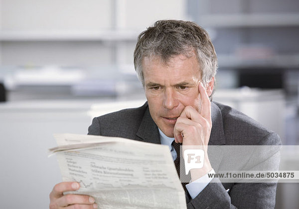 Besorgter Geschäftsmann im Büro liest Zeitung