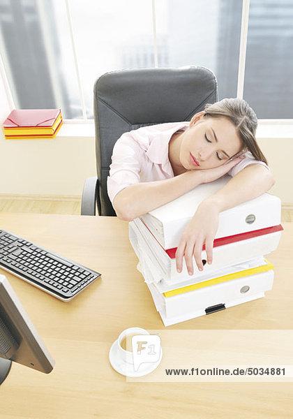 Frau schläft im Büro auf Stapel Aktenordner