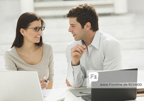 Mann und Frau am Arbeitsplatz  sitzen vor Laptops