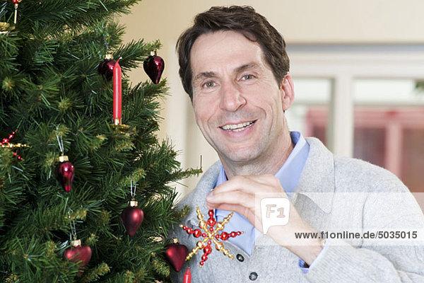 Man decorating Christmas tree  Munich  Bavaria  Germany