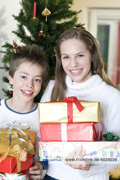 Glückliche Geschwister mit Weihnachtsgeschenken  München  Bayern  Deutschland