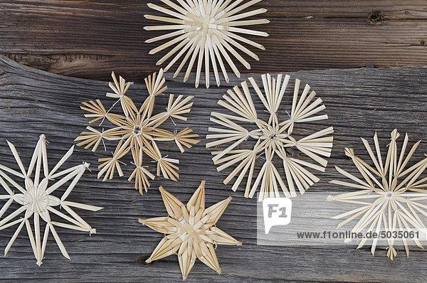 Nahaufnahme eines Strohsterns zur Weihnachtsdekoration am Baumstamm