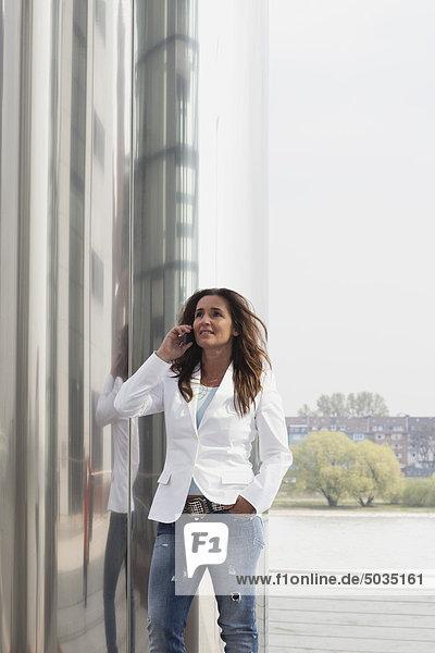 Frau auf dem Handy beim Spaziergang am Rhein