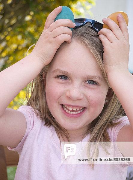 Nahaufnahme eines Mädchens  das mit Ostereiern scherzt  lächelnd