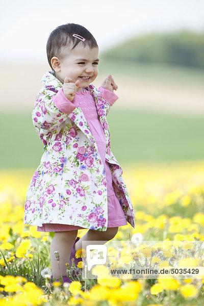 Baby girl walking in flower field  smiling