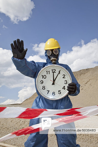 Mann in Schutzbekleidung mit Uhr bei Sanddüne und Kordonband im Vordergrund