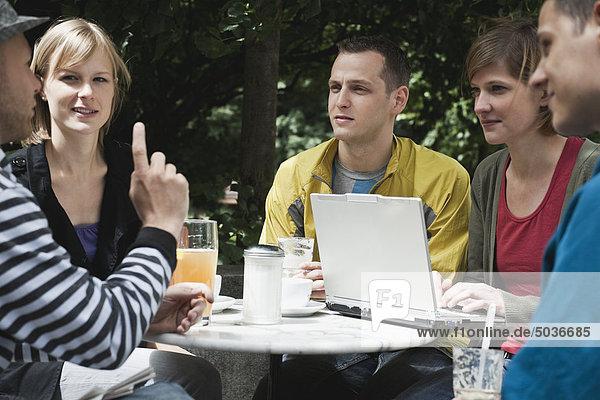 Mann und Frau diskutieren gemeinsam und nutzen den Laptop