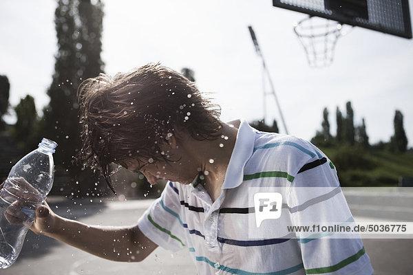 Teenager-Junge  der Wasser in Flaschen gießt. Teenager-Junge, der Wasser in Flaschen gießt.