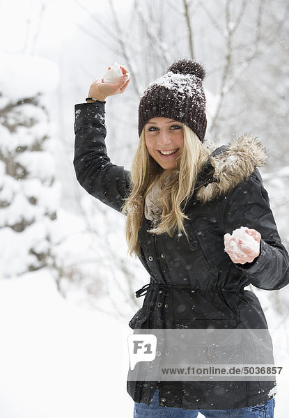 Austria  Teenage girl with snowball  smiling  portrait