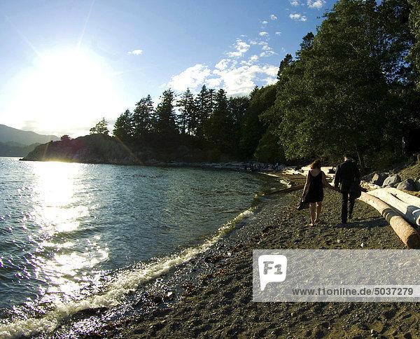 Gut gekleideter Mann und Frau zu Fuß auf felsigen Strand hält hände auf spät Sommernachmittag