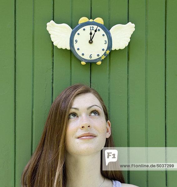 Junge Frau blickte zu eine geflügelte Uhr (Time Flies)  Ontario  Kanada