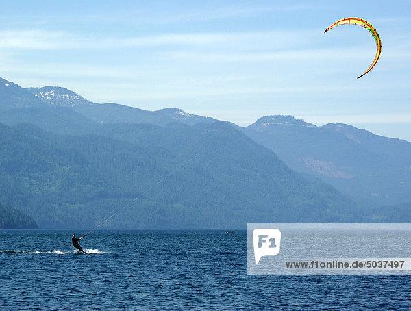 Mann im Anzug Kitesurfing in Ferne auf Harrison Lake in b.c.  Kanada