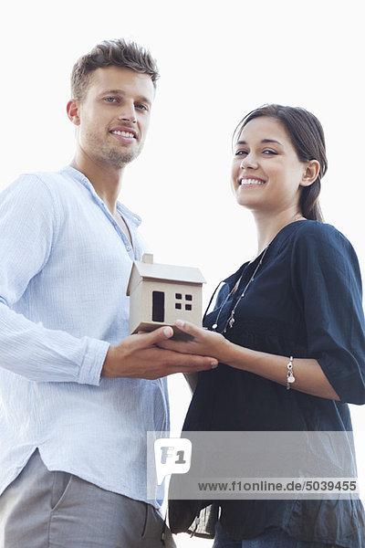 Porträt eines jungen Paares mit kleinem Musterhaus