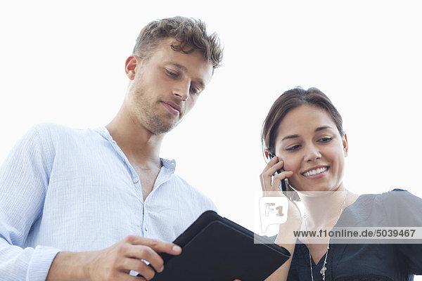 Low-Winkel-Ansicht eines jungen Paares mit elektronischen Gadgets