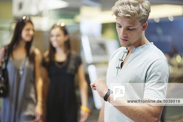 Junger Mann  der die Zeit mit zwei Frauen im Hintergrund in einem Bekleidungsgeschäft überprüft.