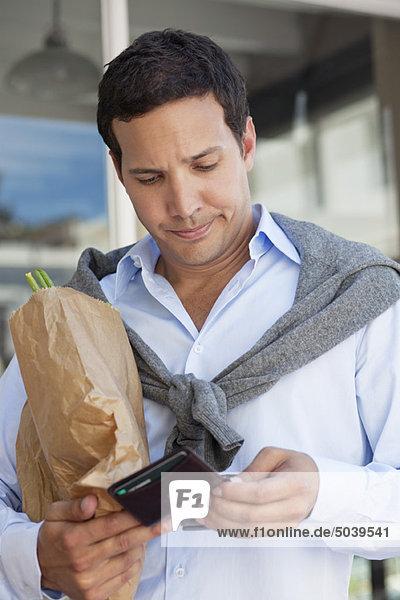 Mittlerer erwachsener Mann  der die leere Brieftasche mit einer Papiertüte voller Gemüse überprüft.