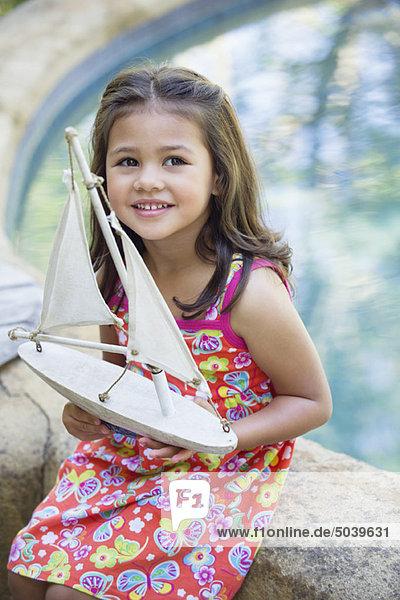 Kleines Mädchen sitzend am Swimmingpool mit Bootsmodell in der Hand