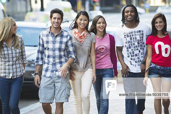 Freunde  die auf dem Bürgersteig gegen Autos laufen.