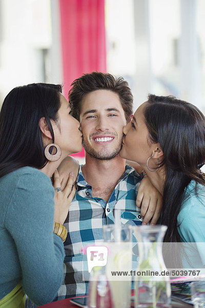 Man being kissed by two women in a restaurant