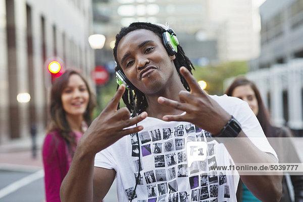 Porträt eines Afroamerikaners beim Musikhören mit Freunden im Hintergrund