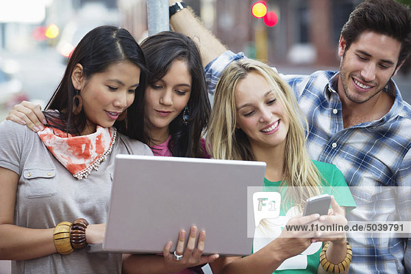 Friends using electronic gadgets outdoors