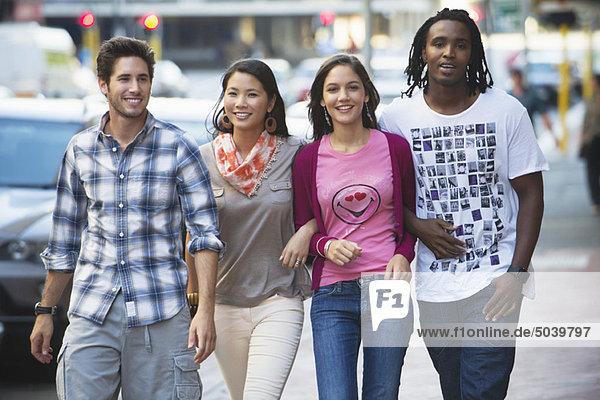 Freunde gehen auf der Straße gegen Autos