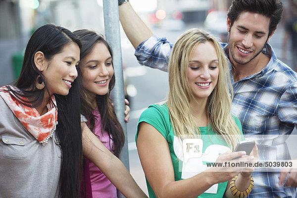Freunde  die ein Handy im Freien benutzen