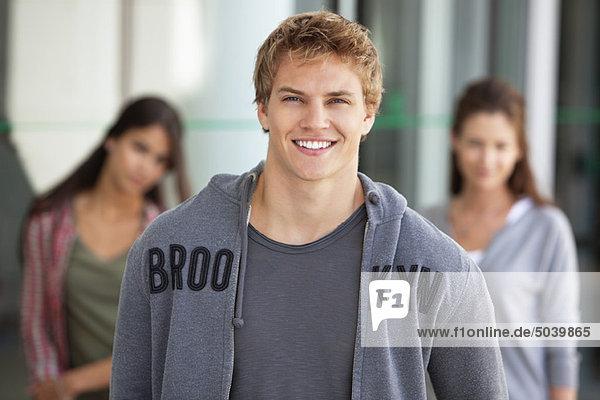 Porträt eines lächelnden Mannes auf dem Campus