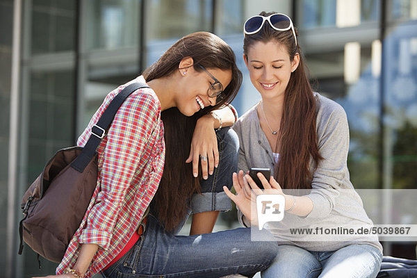 Two female friends reading text message on a mobile phone