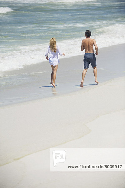 Rear view of a couple running on the beach