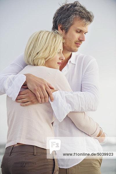 Ein erwachsener Mann  der seine Frau umarmt.