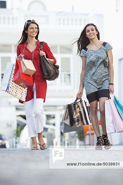 Two young women walking with shopping bags