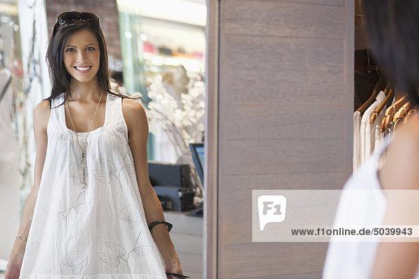 Porträt einer schönen jungen Frau  die ein Kleid im Spiegel anprobiert.
