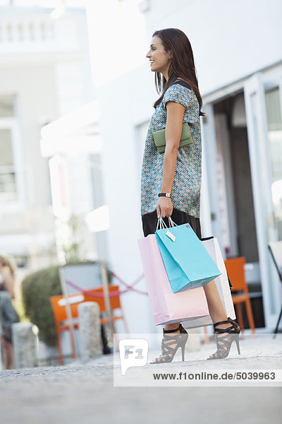 Side profile of a young woman holding shopping bags