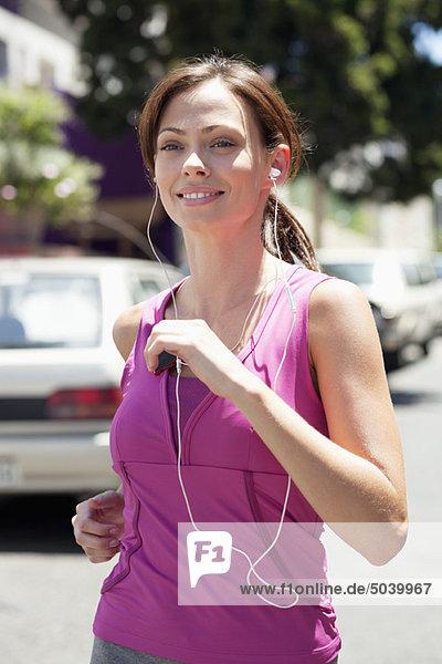 Schöne junge Frau  die beim Joggen mp3-Player hört.