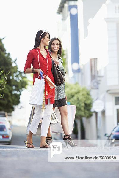 Zwei junge Frauen  die mit Einkaufstaschen gehen.