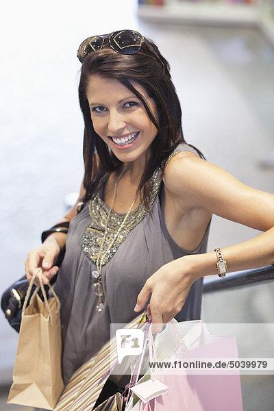 Porträt einer jungen Frau mit Einkaufstaschen