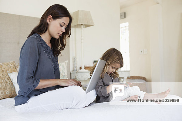 Frau arbeitet an einem Laptop  ihre Tochter spielt mit einem Handy neben ihr.