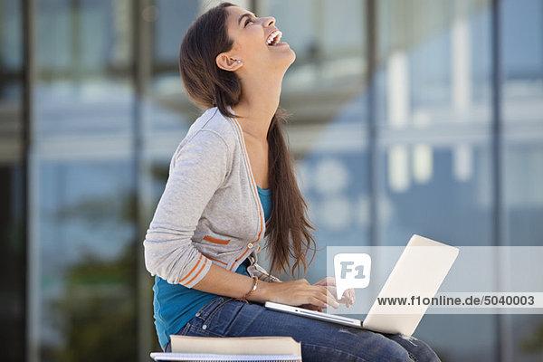 Frau lacht bei der Benutzung eines Laptops