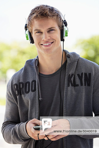 Man listening to music with headphones and smiling