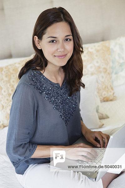 Schöne junge Frau mit einem Laptop zu Hause
