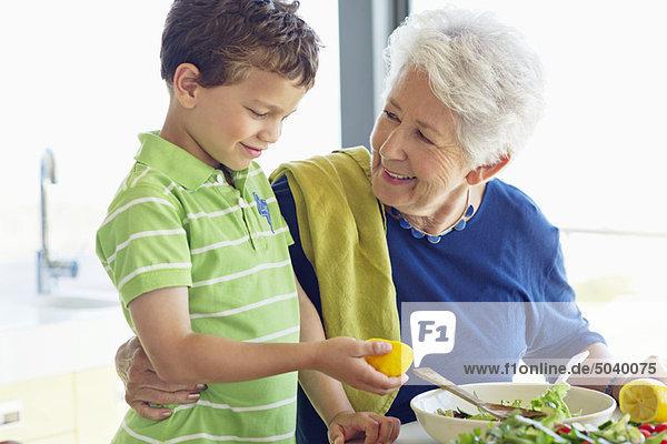 Seniorin bei der Zubereitung des Essens in der Küche mit ihrem Enkel