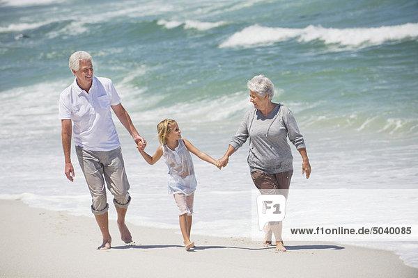 Seniorenpaar  das mit seiner Enkelin am Strand spazieren geht.