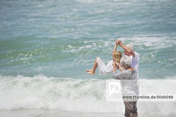 Seniorenpaar hebt ihre Enkelin am Strand in die Luft